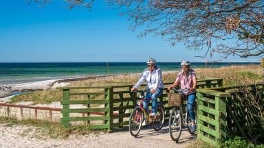 Två cyklister på grusväg vid havet.