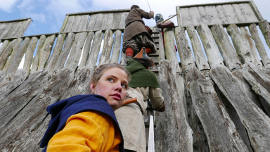 Vikingar klättrar upp för Vikingaborgen i Trelleborg