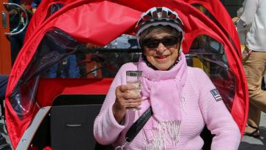 Äldre dam med cykelhjälm och solglasögon sitter i passagerarsäte på en elcykel.