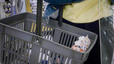 Person i affär håller en kundkorg som innehåller matvaror.