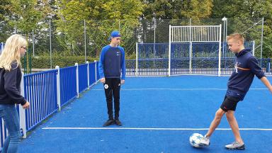 Tre elever på Pilevallskolans fotbollsprofil spelar fotboll.