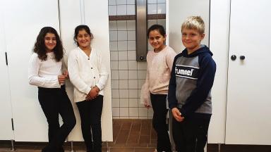 Tre flickor och en pojke i årskurs 4 på Pilevallskolan visar de nya låsbara duschdörrarna.
