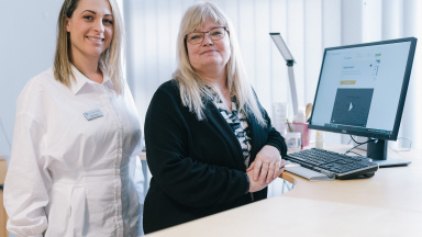 Två kvinnor står vid sidan om ett skrivbord med datorskärm.