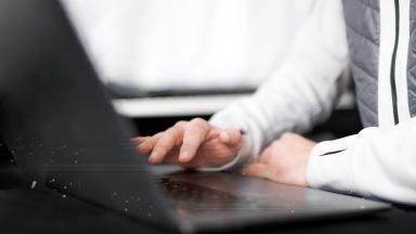 En hand trycker på tangentbordet på en dator.