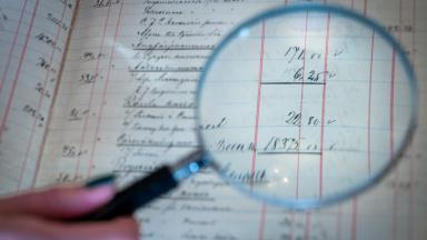Förstoringsglas hålls över dokument med text och siffror