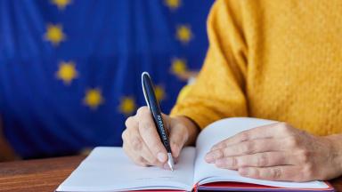 Person håller i EU-penna och skriver i ett block med EU-flaggan i bakgrunden.