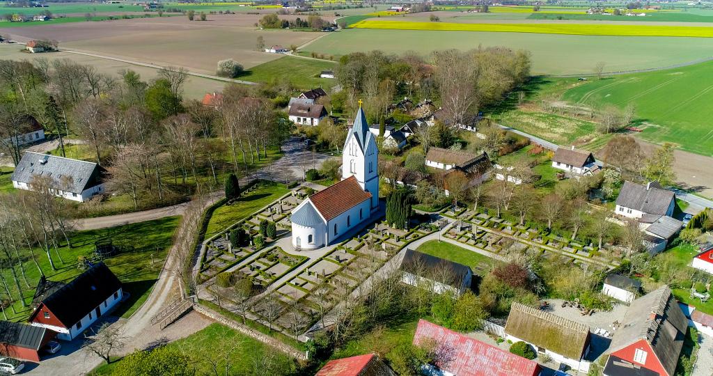 Flygbild över Äspö kyrka med omgivande bebyggelse.