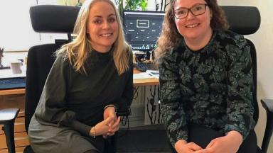 Två kvinnor sitter framför ett skrivbord med datorskärm.