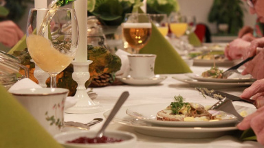 Matbord med vit duk, glas, tallrikar och servetter.