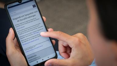 Person sitter med mobiltelefon i sin hand.