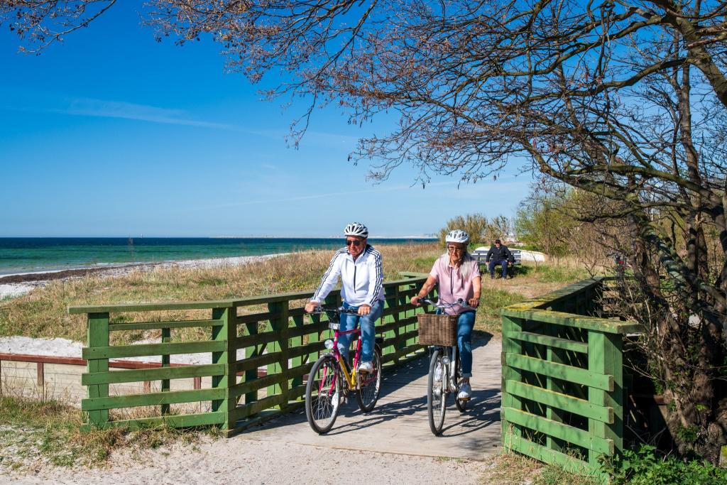 Två personer cyklar på en grusstig längs havet.