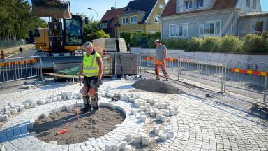 Gatuarbetare och grävskopa vid pågående beläggningsarbete