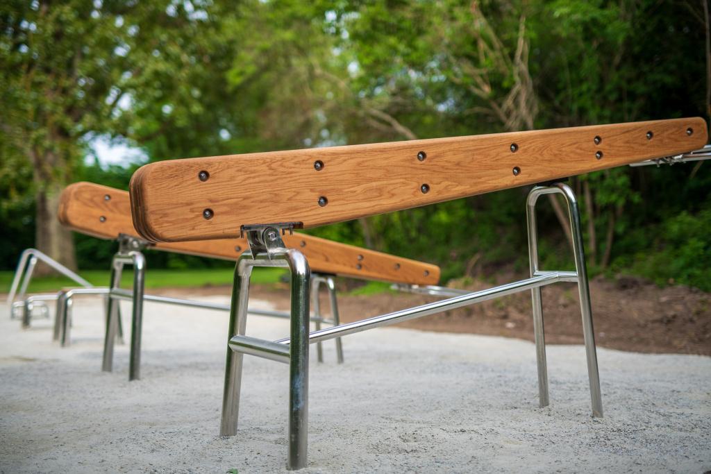 Redskap i rostfritt stål och ek står på en bädd av grus.