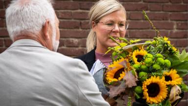 Bildningsnämndens ordförande Lars Mikkelä (M) överlämnar en bukett solrosor till rektor Anna Malmquist.