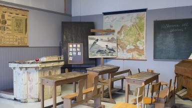 Gammaldags skolsal med bänkar, kateder, griffeltavla och planscher.